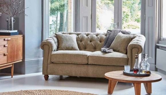 The Wantage 2 Seater Sofa Bed in Stain Resistant Chenille Army Green with dark oak feet