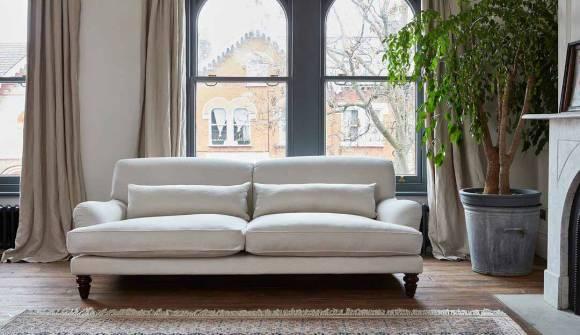 The aberdeen midi sofa in 100% linen candle with dark oak feet