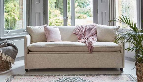 The Norbury 3 Seater Sofa Bed in Washed Cotton Clay with dark oak feet
