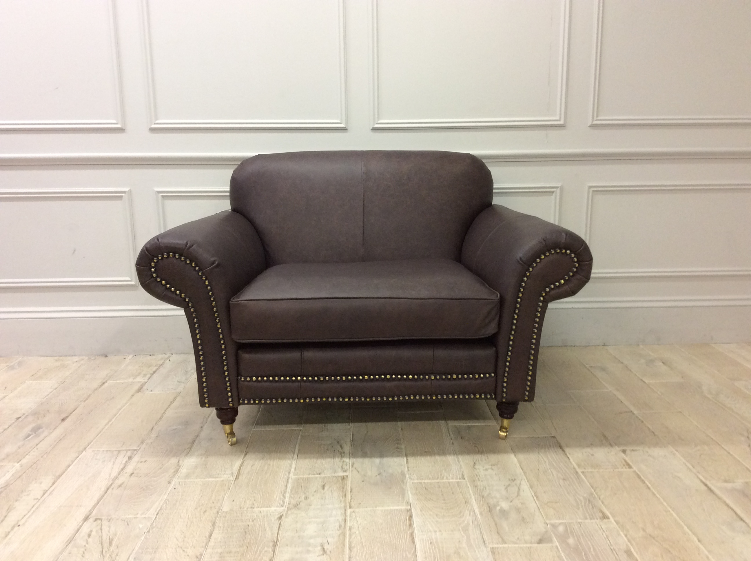 Product photograph showing Chelsea 1 5 Seater Chair In Dune Coffee Leather With Studding And Castors